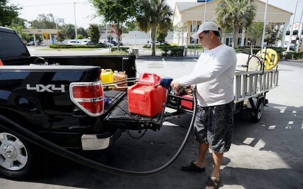 ポリタンクでガソリンを持ち帰る男性(12日、フロリダ州)=ロイター
