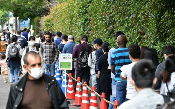東京出入国在留管理局前に並ぶ在留外国人ら