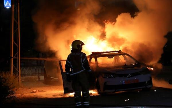 アラブ系住民との衝突が起きたイスラエル中部ロッドで炎上する車(12日)=ロイター