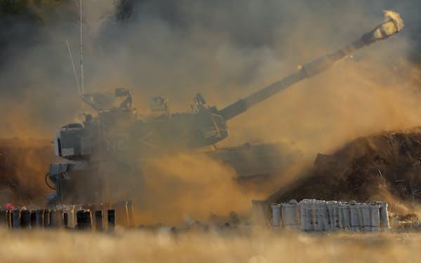 ガザ地区に向けて砲撃するイスラエル軍(13日)=AP