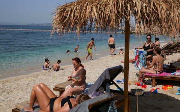 ビーチでくつろぐ人々(8日、ギリシャ・アテネ)=ロイター