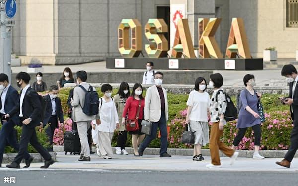 大阪市役所前を歩くマスク姿の人たち(14日午後)=共同