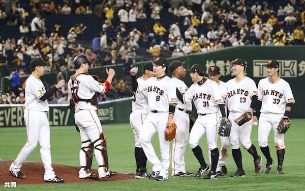 通算2000試合目の阪神戦で勝利し、タッチを交わす巨人ナイン(15日)=共同