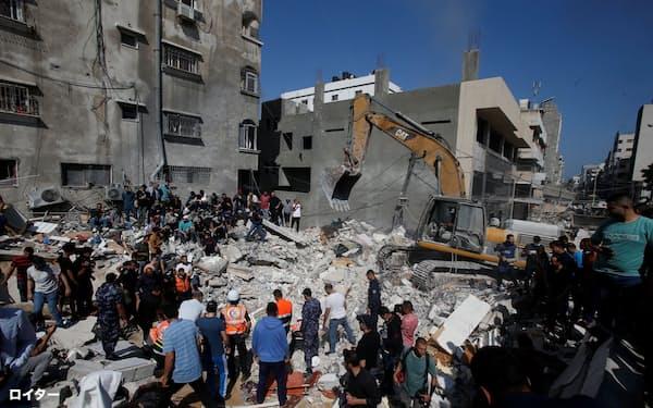 16日、ガザでは空爆で破壊された建物跡で生存者を捜す救助活動が行われた=ロイター