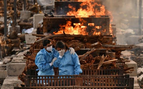 インド・ベンガルールで新型コロナ感染症により死亡した人の火葬に立ち会う家族=ロイター