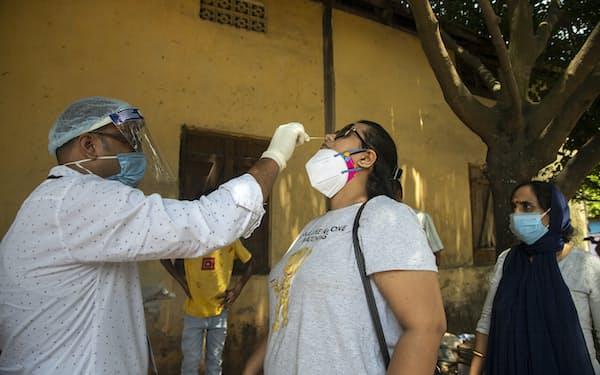 インドでは新型コロナの感染者数が高止まりする(14日、検査を受ける女性)=AP