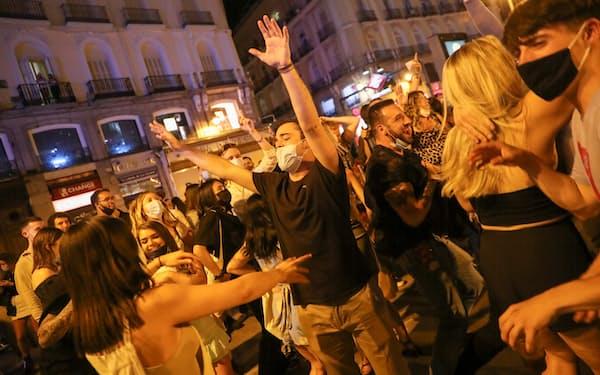 非常事態宣言解除の前夜、マドリードのプエルタ・デル・ソル広場で喜びの声を上げる若者たち=ロイター