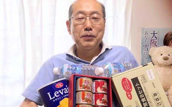 株主優待でもらった備蓄品を持つ桐谷さん