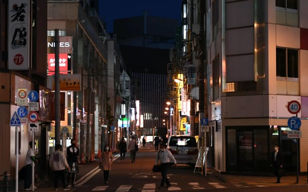 消灯した店舗の看板が目立ち閑散とする飲食店街(6日、東京都千代田区)