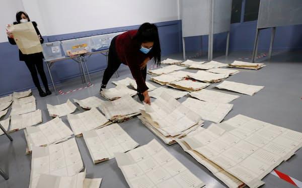 投票結果を分類する選挙管理当局の職員(16日、中部バルパライソ)=ロイター