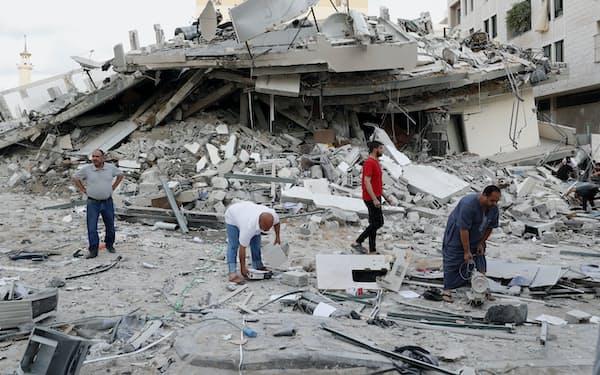 イスラエルの空爆で破壊された住居を調べる人々(17日、ガザ)=AP