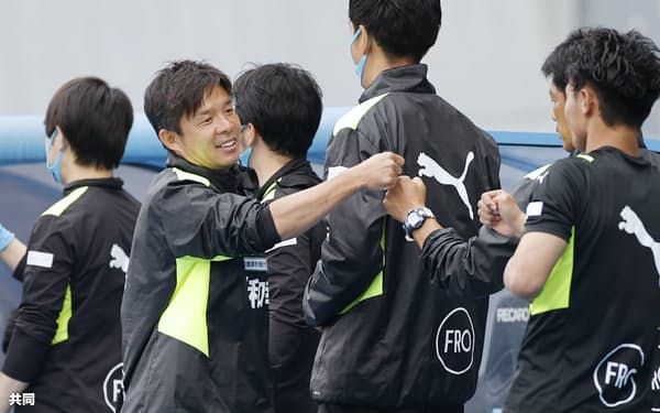 札幌戦の勝利で昨季から22戦無敗のJ1新記録を打ち立て、タッチを交わす川崎・鬼木監督(左から2人目、16日)=共同