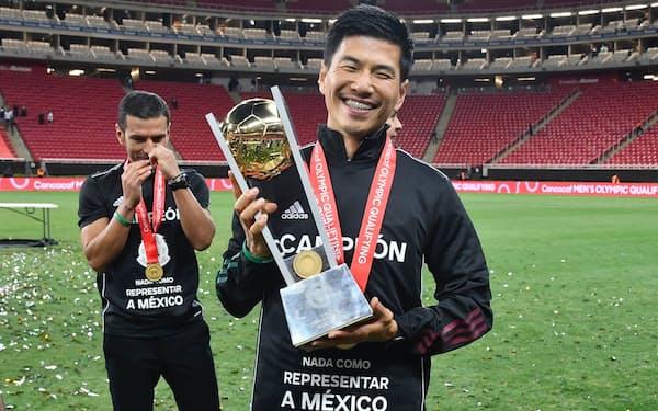 五輪代表を決める北中米カリブ海予選の優勝カップを持つ西村㊨と監督のロサノ=メキシコ・サッカー連盟提供