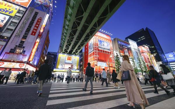繰り返す緊急事態宣言で経済の回復は遠のく。東京・秋葉原の横断歩道を行き交うマスク姿の人たち=共同