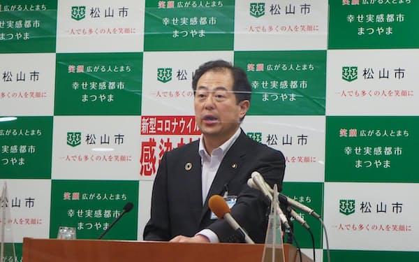 記者会見に臨む野志克仁市長(18日、松山市)