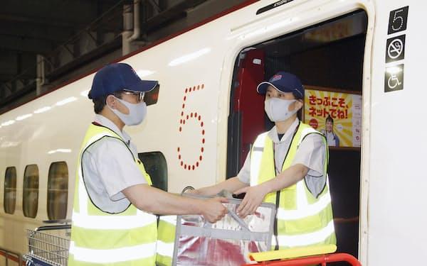 鹿児島中央へ搬送するため、九州新幹線に積み込まれる荷物(18日午後、JR博多駅)=共同