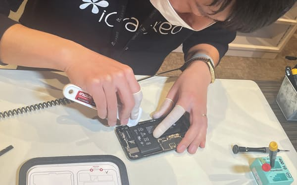 アップルは日本でもIRPを始める(写真は独立系修理会社がスマホを修理する様子)