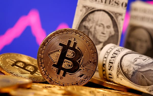 FILE PHOTO: A representation of virtual currency Bitcoin and U.S. One Dollar banknotes are seen in front of a stock graph in this illustration taken January 8, 2021. REUTERS/Dado Ruvic/File Photo