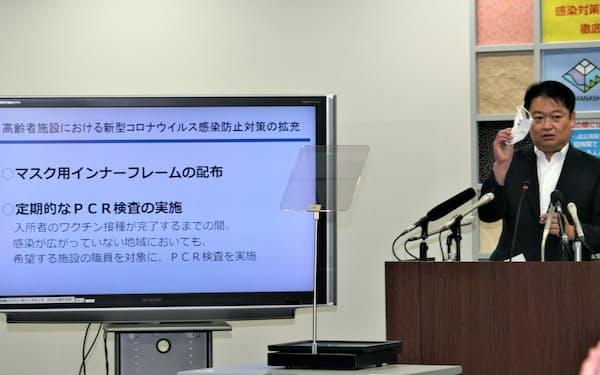 高齢者施設に配布するマスクのインナーフレームを手に施設の感染対策について説明する山梨県の長崎幸太郎知事(20日、甲府市内)