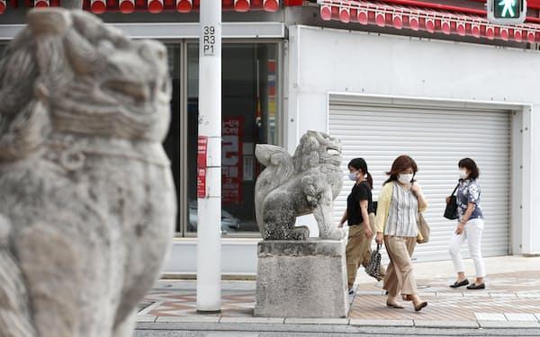 那覇市の国際通り付近をマスク姿で歩く人たち。営業していない店が目立った(20日午後)=共同