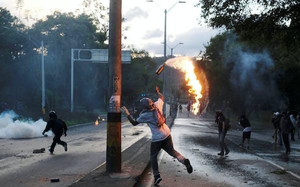 火炎瓶を投げ、政府に抗議する人々(19日、メデジン)=ロイター