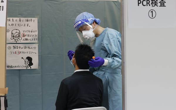 成田空港で帰国・入国者のPCR検査を行う検疫担当者(2020年6月)=共同