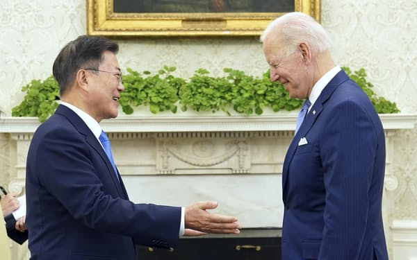 21日、ホワイトハウスで言葉を交わすバイデン米大統領(右)と韓国の文在寅大統領=聯合・共同