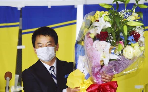さいたま市長選で4選を果たし、花束を掲げる清水勇人氏=23日夜、さいたま市