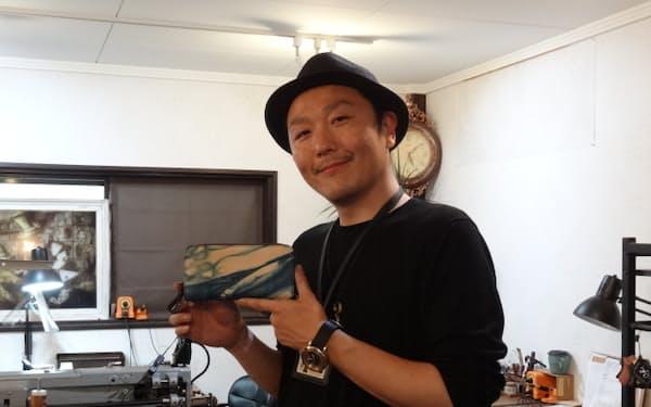 「福山レザー」を使った財布を手にする三島進