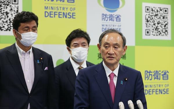 自衛隊東京大規模接種センターの視察を終え、記者の質問に答える菅首相。左端は岸防衛相(24日、東京都千代田区の大手町合同庁舎3号館)