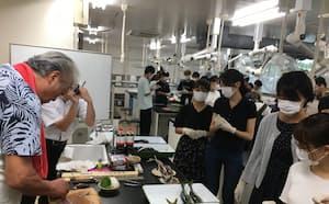 講師の西潟さんの手さばきを見る学生(2019年)