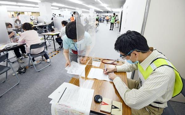 神戸市の大規模接種会場で予診票を確認する医師(右)=25日午後、神戸市中央区