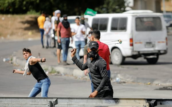 イスラエル部隊に投石するパレスチナ人の若者ら(ヨルダン川西岸ナブルス近郊)=ロイター