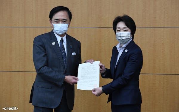 神奈川県の黒岩祐治知事㊧が組織委の橋本聖子会長に提言書を手渡した(27日、東京・中央)