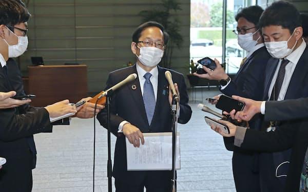 記者の質問に答える公明党の竹内政調会長(中央)=共同