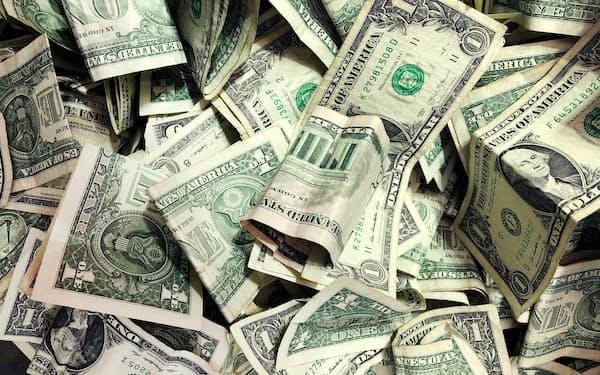 基軸通貨ドルの異例の実質マイナス金利がマネーを半ば強制的にリスク投資に押し出してきた(洗車場のチップ入れ場に投げられた米ドル札、米ニューヨーク)=AP