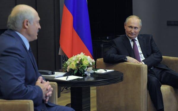 28日、ロシア南部の保養地ソチで会談するプーチン大統領㊨とルカシェンコ大統領=AP