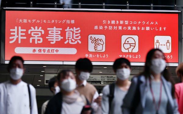 「大阪モデル」の非常事態を表示するJR大阪駅前の大型ビジョン(28日、大阪市北区)