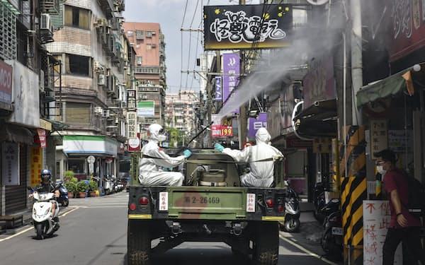 新型コロナ感染者が急増する台湾では、ワクチンの入手を巡り論争が続く=AP