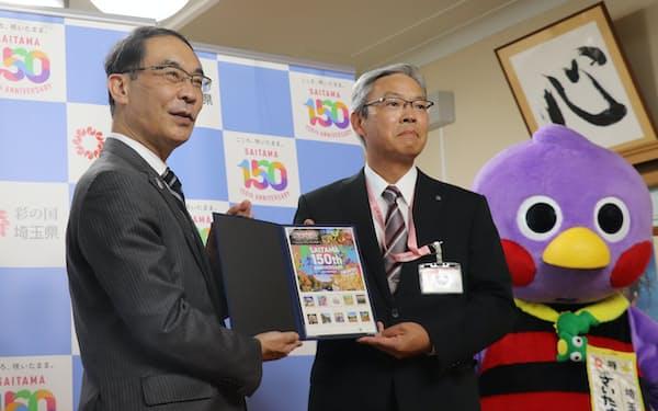 埼玉県150周年記念切手セット販売の報告を受けた大野元裕知事(左、埼玉県庁)