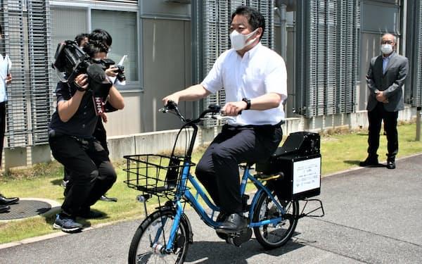 燃料電池の電動アシスト自転車に試乗する山梨県の長崎幸太郎知事(31日、山梨大学燃料電池ナノ材料研究センター)