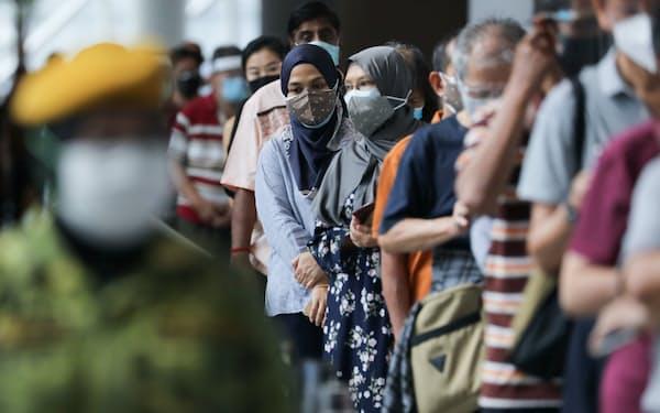 5月31日、マレーシアの首都クアラルンプールで新型コロナウイルスのワクチン接種に並ぶ人々=ロイター