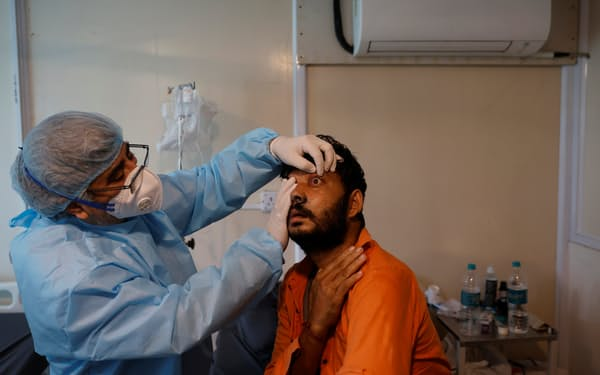 Doctor Brajpal Singh Tyagi checks the eyes of Adesh Kumar, 39, who is suffering from Mucormycosis also known as black fungus, at Harsh ENT hospital in Ghaziabad, on the outskirts of New Delhi, India May 31, 2021. REUTERS/Adnan Abidi