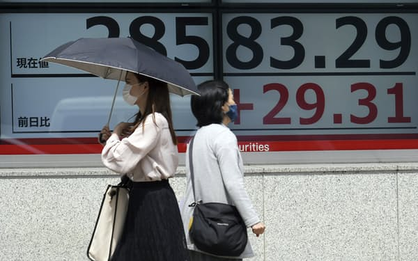 Women wearing protective masks walk in front of an electronic stock board showing Japan's Nikkei 225 index at a securities firm Wednesday, May 26, 2021, in Tokyo. Asian stock markets rose Wednesday as inflation fears eased and investors looked ahead to U.S. data that are expected to show economic growth accelerating. (AP Photo/Eugene Hoshiko)