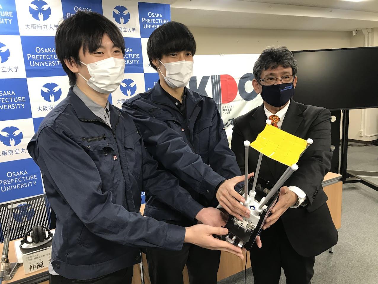 大阪府立大学小型宇宙機システム研究センターが開発した超小型衛星「ひろがり」の模型を持つメンバー(㊨が小木曽望教授)
