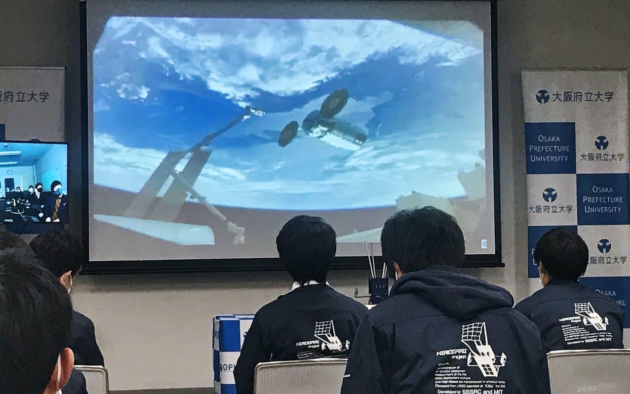 超小型衛星「ひろがり」を搭載したロケットと国際宇宙ステーションのドッキングを見守る大阪府立大のメンバー。ロケットの背景は地球(2月22日、堺市)
