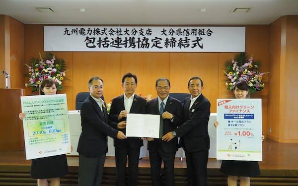 包括連携協定を結んだ大分県信組の吉野理事長(右から3人目)と九電の和仁執行役員大分支店長(同4人目、2日、大分市)