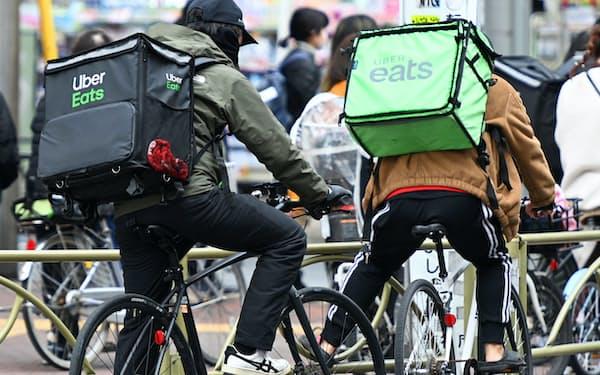 街中を自転車で走るウーバーイーツの配達員(東京都世田谷区)