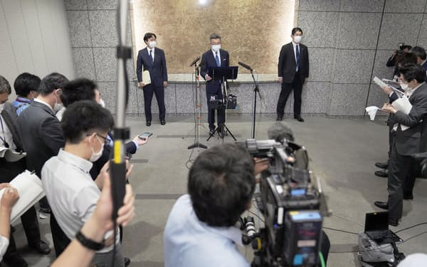 東北新社の外資規制違反問題で記者会見する武田総務相(奥中央、4日、総務省)=共同