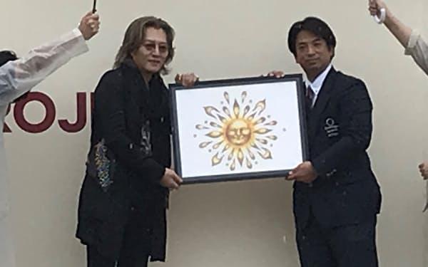 石井竜也さん(左)が自らデザインしたプロジェクトのロゴを披露した(行方市)